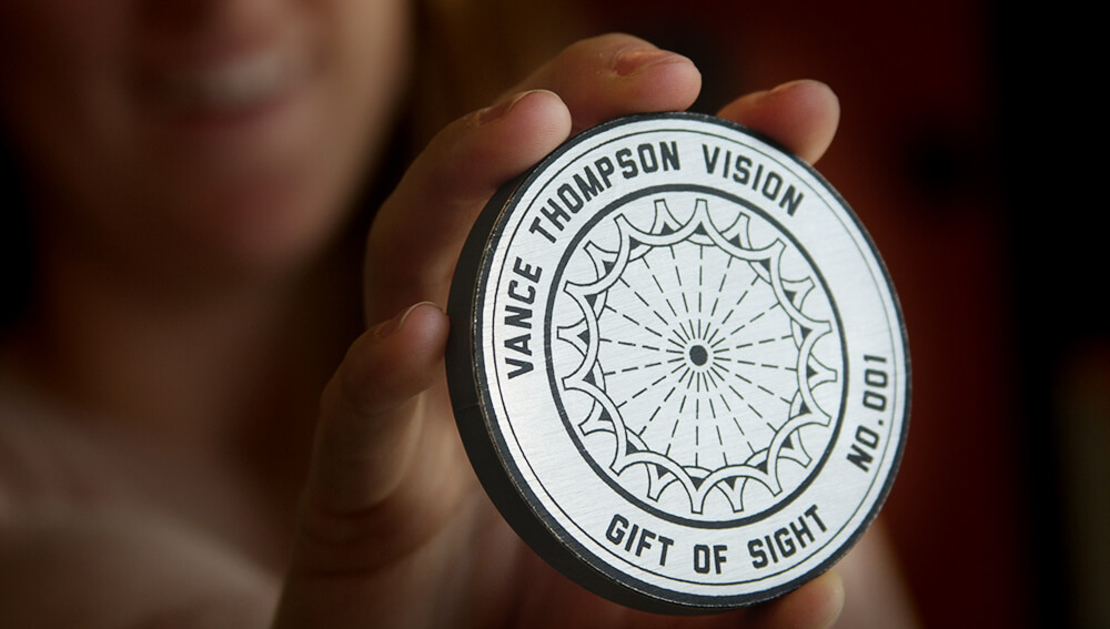 Woman holding Gift of Sight medallion
